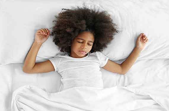 Young girl sleeping in bed.